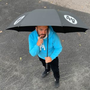 44 Teeth black umbrella with white logo print held by Alastair Fagan